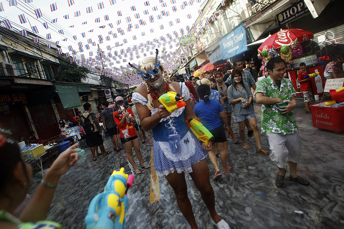A reveller uses a water gun as he participates in a water fight during the Songkran Festival celebration at Khaosan road in Bangkok
